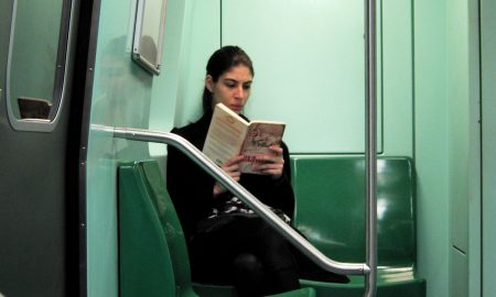 Woman reading book on subway