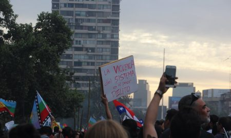 "Image of protesters in Chile. The protester's sign reads ""La violencia del sistema es el peor delito"""