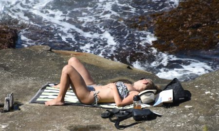 Woman sunbathing on cliff over ocean