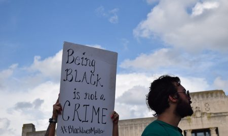 "Activist holding protest sign that reads ""Being black is not a crime #black lives matter"""